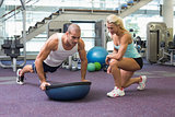 Female trainer assisting man with push ups at gym