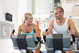Fit couple working on exercise bikes at gym