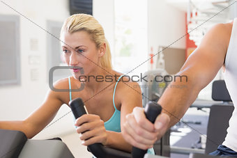 Fit young couple working on exercise bikes at gym