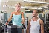 Male trainer assisting woman with exercise bike at gym