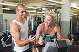 Trainer timing his client on exercise bike at gym