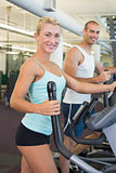 Fit young couple working on x-trainers at gym