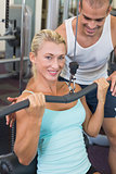 Male trainer assisting beautiful young woman on lat machine