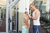 Trainer assisting young woman on a lat machine in gym