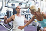 Trainer assisting man on fitness machine at gym