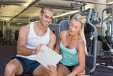 Woman discussing her performance on clipboard with trainer at gym