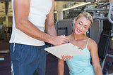 Woman discussing her performance on clipboard with a trainer at gym