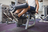 Fit man using weights machine for legs