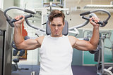 Fit man using weights machine for arms