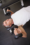 Fit man lifting dumbbells lying on the bench