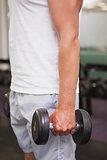 Fit man lifting heavy black dumbbell