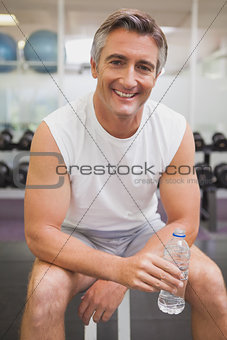 Fit man taking a break in the weights room