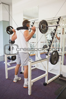 Fit man lifting heavy barbell