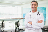 Confident doctor standing in fitness studio