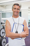 Fit personal trainer smiling at camera in fitness studio