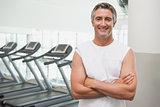 Fit man smiling at camera beside treadmills