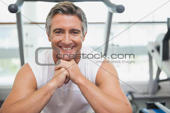 Fit man smiling at camera in fitness studio