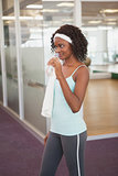 Fit woman drinking water in fitness studio