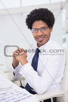 Handsome photo editor working at desk