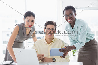 Casual business team looking at tablet together