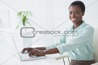 Happy businesswoman using her laptop
