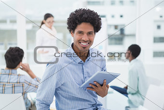 Casual businessman holding his tablet