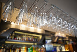 Many wine glasses hanging above the bar