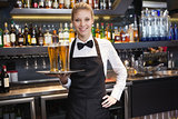 Waitress with hand on hip holding a tray of champagne