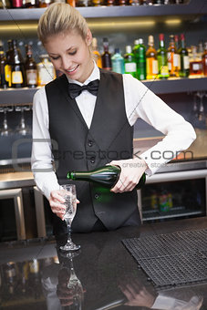 Cute woman in suit pouring champagne into flute