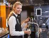 Barmaid pulling a glass of beer while looking at camera