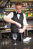 Handsome waiter opening a bottle of red wine