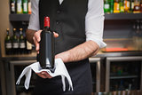 Handsome waiter holding a bottle of red wine