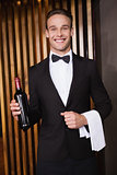 Handsome waiter holding a bottle of red wine and a towel