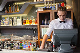 Handsome barman standing at the cash register