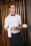 Smiling waiter holding tray with coffee cup and pint of beer
