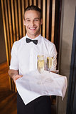 Handsome smiling waiter holding tray of champagne