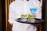 Cheerful young waiter holding tray with cocktails