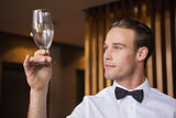 Handsome waiter inspecting a wine glass