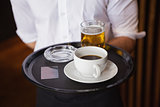 Waiter holding tray with coffee cup and pint of beer