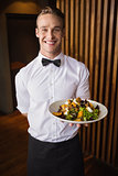 Smiling waiter showing plate of salad to camera