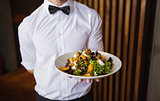 Waiter showing plate of salad to camera