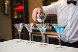Bartender pouring blue alcohol into cocktail glass