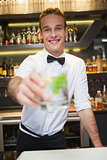 Happy bartender offering cocktail to camera