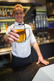 Smiling bartender offering pint of beer to camera