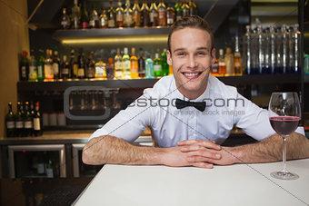 Smiling bartender having glass of red wine