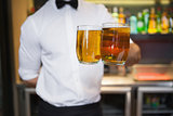 Bartender holding two glasses of beer