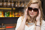 Pretty blonde woman in sunglasses posing