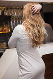 Rear view of pretty blonde girl posing hands in the hair