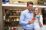 Cute couple standing and drinking cocktails