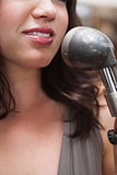 Smiling brunette singing with her microphone